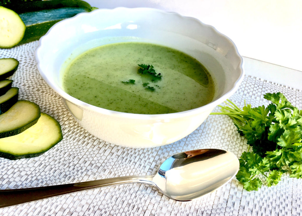 Zucchinicremesuppe in Schüssel mit silbernen Löffel